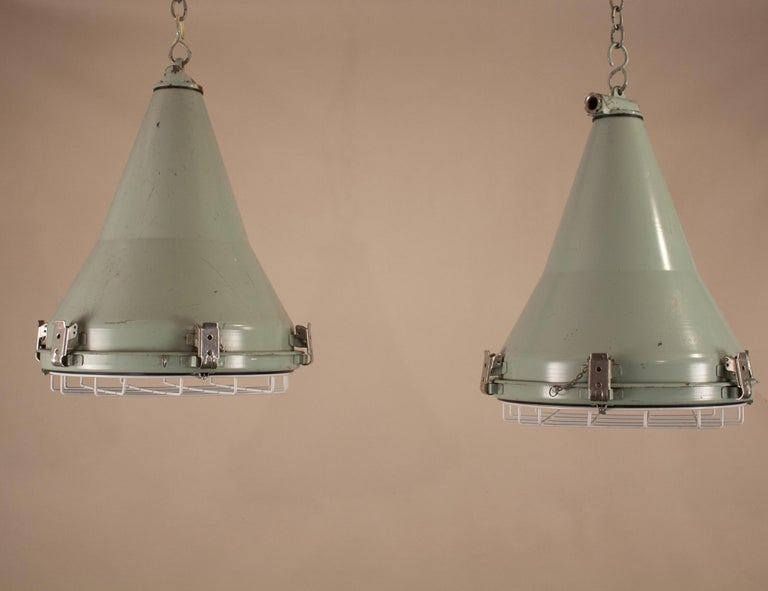 A pair of 1970s maritime aluminum pendant lights with conical form and original putty-green paint. Salvaged from a cargo ship near the Bay of Bengal, these authentic nautical lights bear the stamp of Daeyang Electric, South Korea. The white