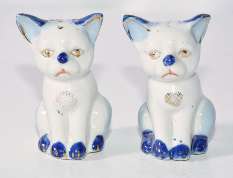 The pair of vintage kitty salt and pepper shakers are blue and white with gilt detailing. Holes on bottom for filling spices.