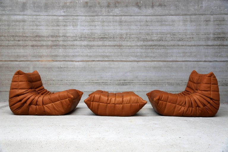 Two single seat lounge chairs and pouf, model Togo from Ligne Roset designed by Michel Ducaroy. Re-upholstered in our signature full grain cognac leather. Our leather is biologically colored and feels warm and comfortable. Top