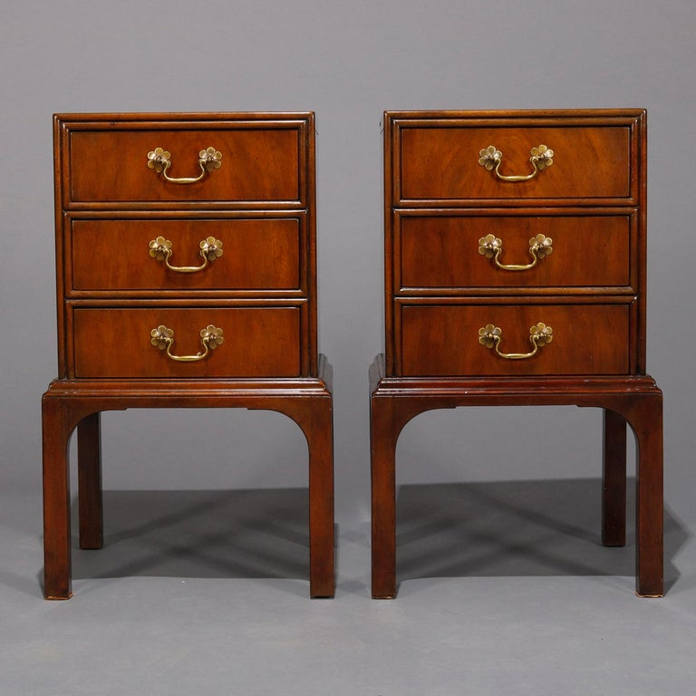 A vintage pair of Chinese Chippendale stands by Kittinger each offer mahogany construction with case having three drawers having pulls with flower form escutcheons, raised on squared and straight legs, marked on drawer interior as photographed,