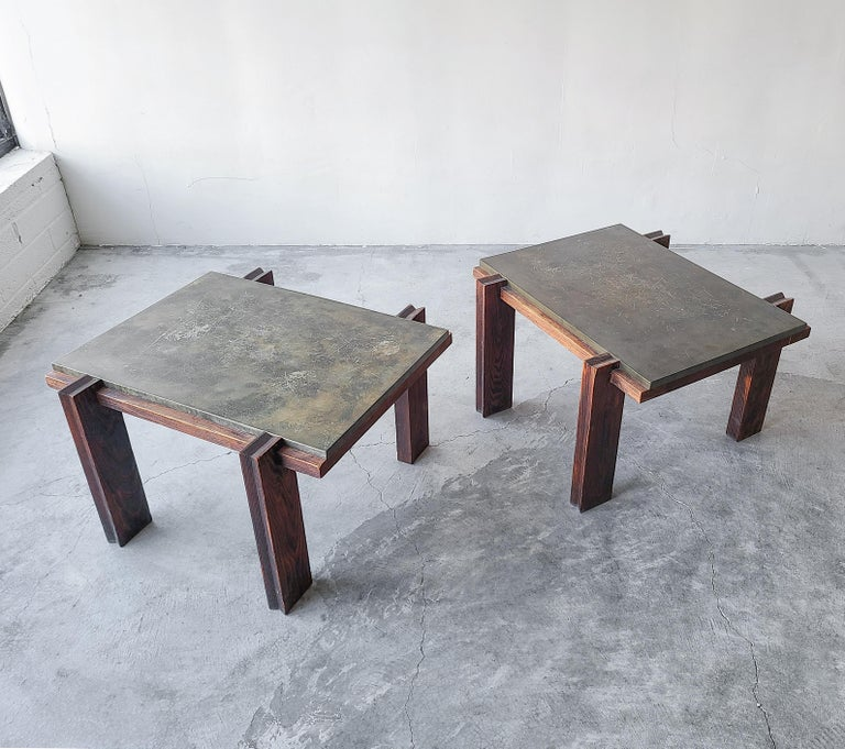 Very unique vintage pair of aged metal and darkened oak side tables. Tables are architecturally interesting with unique carved wood details, very craftsman style feel.