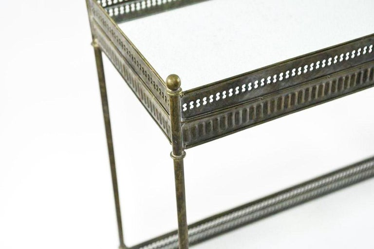 Each of the pair of vintage consoles have two mirrored gallery tray siding. The mottled metal