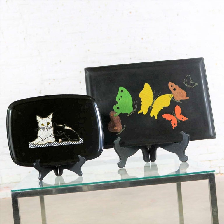 Gorgeous pair of vintage Mid-Century Modern Couroc of Monterey black trays. One tray with inlaid cats with gold accents. And one tray with butterflies. They are in wonderful vintage condition and still retain their Couroc labels one even has its