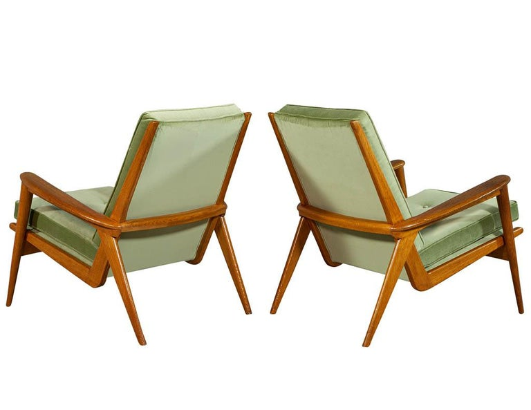 Pair of European oak midcentury lounge chairs with proprietary spring upholstery. In a natural oak finish and satin green fabric.  Price includes complimentary curb side delivery to the continental USA.