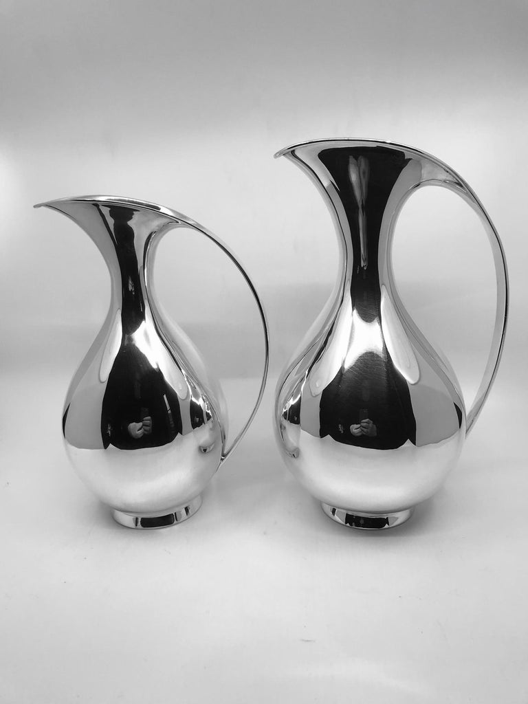 This is a pair of A. Michelsen sterling silver pitchers designed by Kay Fisker in 1935, from a private estate in London. Fisker designed two sizes of this pitcher, both are represented here and sold together. This design has been the forefront and