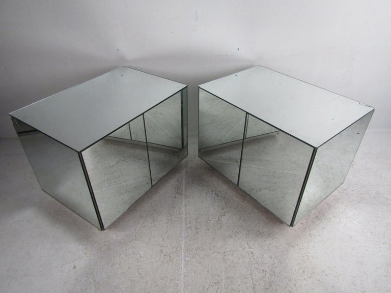 This stunning pair of vintage mirrored cabinets featuring push to open doors revealing ample storage. These unique pieces have multiple sliding drawers along with one adjustable shelf. The mirror finish adds a beautiful touch to this truly hard to