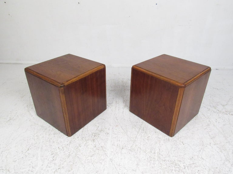 This stylish pair of Mid-Century Modern side tables feature a perfect cubed shape with a vintage walnut finish. This simple, yet sleek pair of tables boast a two-tone design with oak edges complementing walnut wood grain. A convenient side table