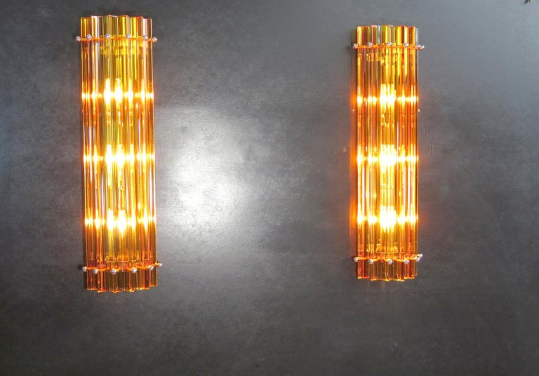 Fantastic pair of vintage Murano wall sconce made by 6 Murano crystal prism (triedri) for each applique in a chrome metal frame. The shape of this sconce is column. The glasses are amber. The wall lamps can be installed vertically, as photos, very