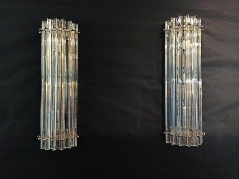 Fantastic pair of vintage Murano wall sconce made by 7 Murano iridescent prism (triedri) for each applique in a chrome metal frame. The shape of this sconce is column. The glasses have the particularity of reflecting a multiplicity of colors, which