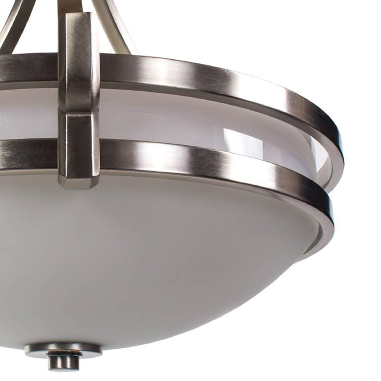Pair of nickel and white glass pendant light fixtures with fixed hanging stem, England, circa 1940. Wired for USA; each light takes a standard U.S. bulb, 100 watts max.  Dimensions: 26 inches wide 20 inches total drop height including canopy.