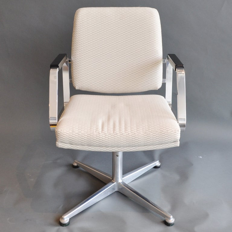 A pair of vintage swivel chairs, beautifully refurbished. The arms are polished chrome with ebony-stained wood arm rests. Each has been newly upholstered in a contemporary fabric to bring them back to their original glory.