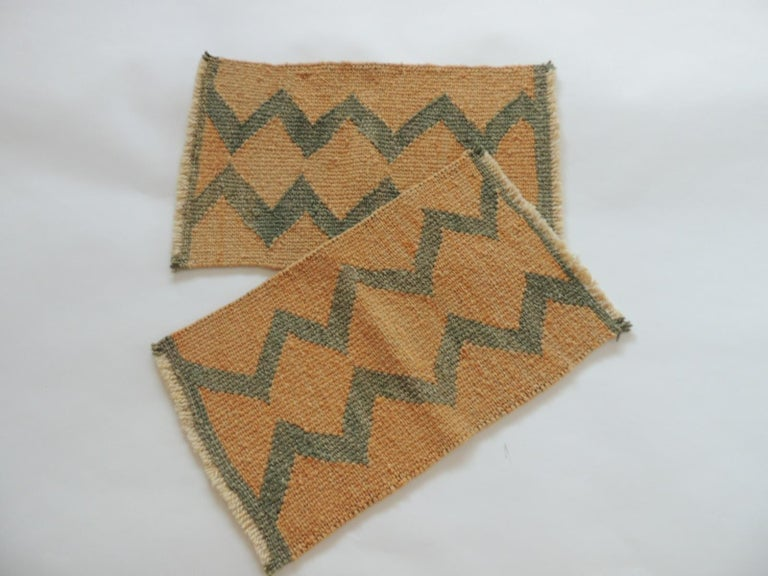 Vintage pale orange and green woven rug samples.