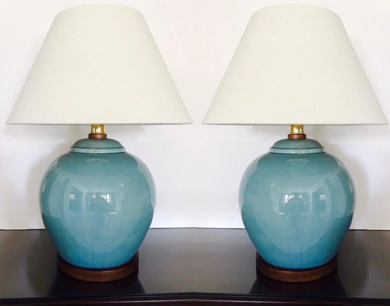 Gorgeous pair of large ceramic pottery lamps in Robin's Egg Blue. The lamps feature a crackle glaze finish with hand-painted trim in cerulean blue and with walnut wood bases and fittings. Fitted with brass sockets and three-way switch and shown with