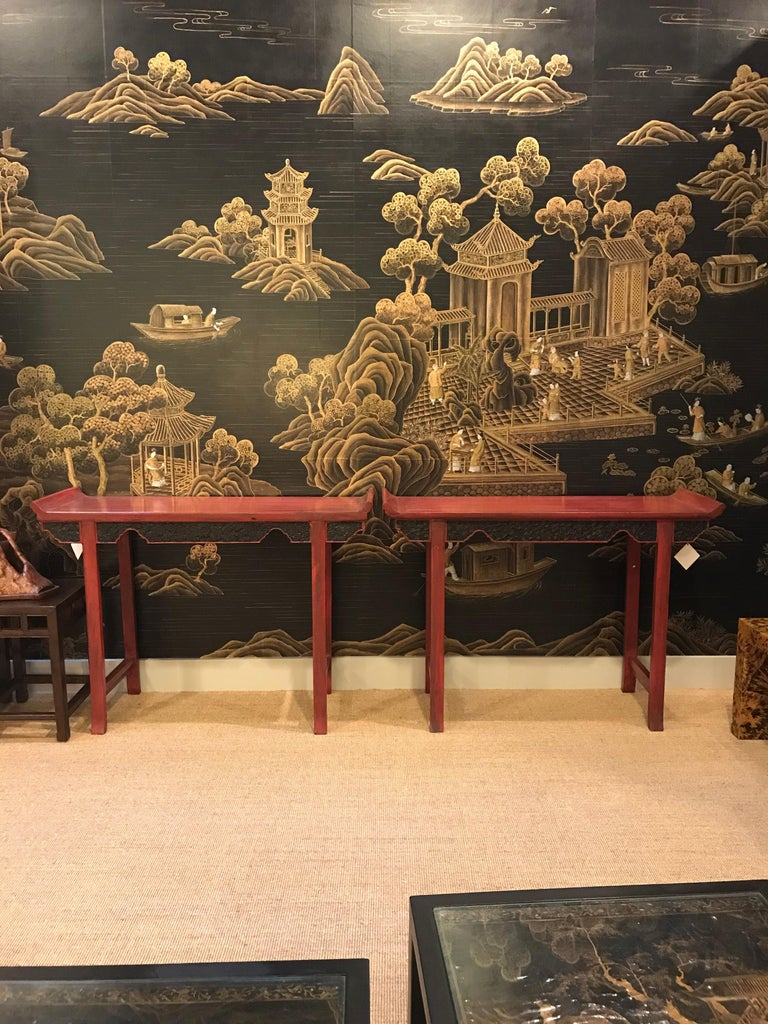 A pair of Chinese red lacquer console tables, available as the pair, or individually.  Finished in deep red lacquer, the aprons have intricate carved design, and the tops have upturned ends.