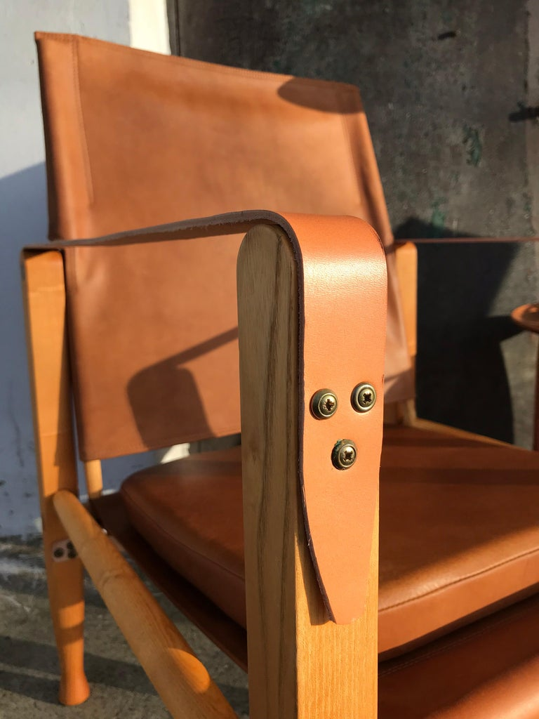 A pair of vintage refurbished safari chairs designed by Kaare Klint for Rud Rasmussen furniture makers. Kaare Klint designed the safari chairs in 1933. These iconic chairs are made of ash and have been professionally refurbished with new anilin