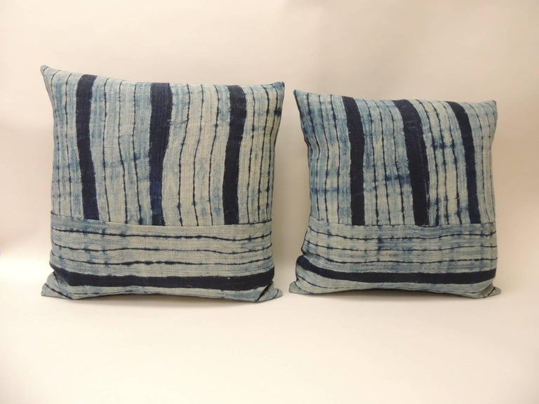 Pair of vintage Shibori stripes blue Asian decorative pillows. Pair of square Indigo stripe homespun hemp textile with dark blue linen backings. Combination of vertical and horizontal stripes to create this unique pattern, Decorative bolster