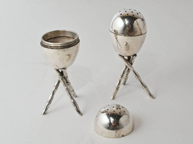 The pair of silver plated salt and pepper shakers are egg shaped and sit on tripods. The tops unscrew.