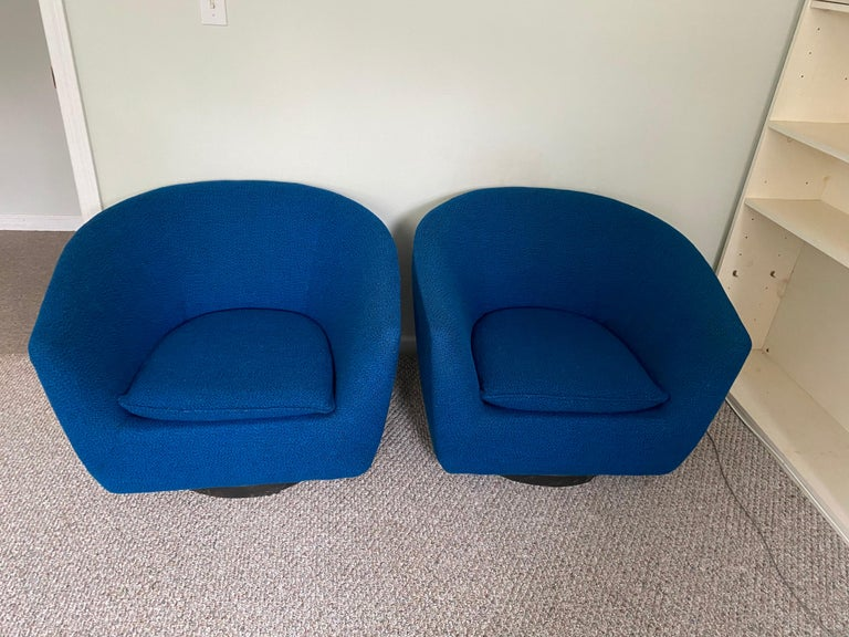 Elegant pair of unsigned vintage swivel lounge chairs, upholstered in the original blue wool. Wider shape than your typical barrel chair from this period. Veneer on base will be redone.