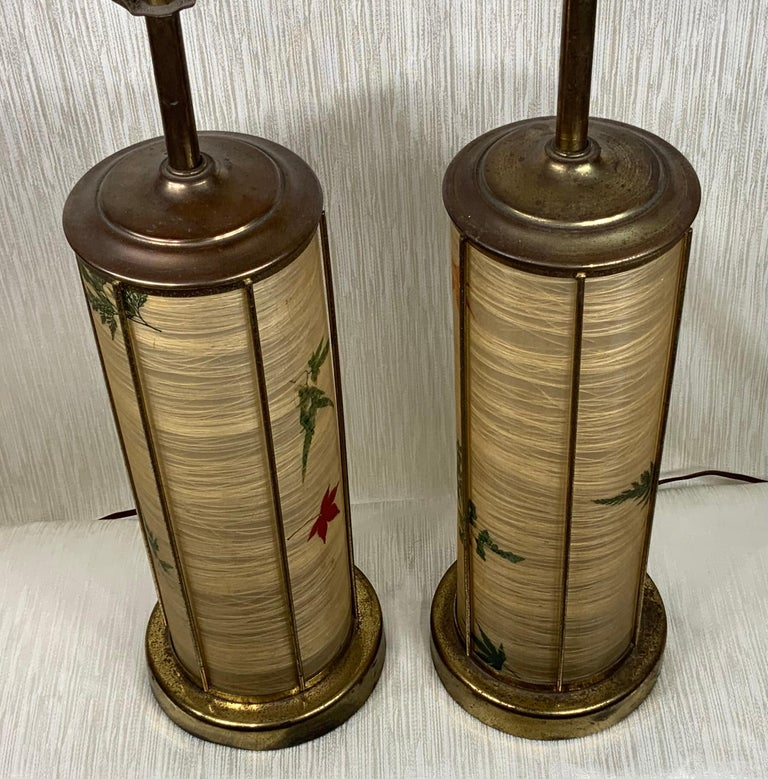 Pair of elegant midcentury table lamps made of brass, with faux parchment shades and base of trees leaves motifs. Included pair of funky lamp finial and three way lighting. Great pair of nostalgic table lamps.