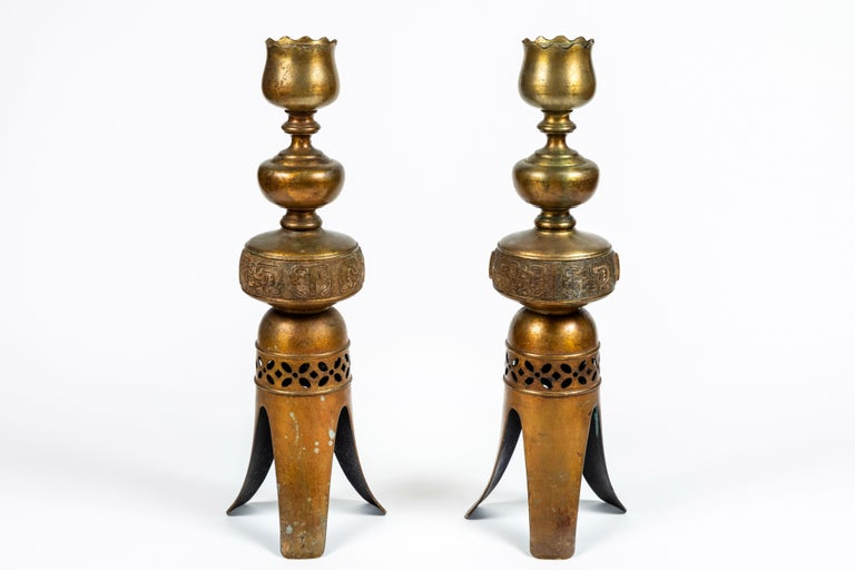 A pair of outstanding tall vintage intricately decorated metal candleholders with gold finish, 3-leg base with pierced design accent and possible Peruvian motif center detailing. Measures: 20.5