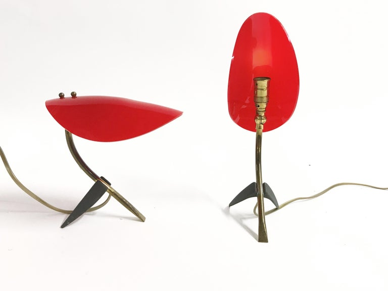 Wonderful pair of italian tripod base table lamps.  The lamps have a brass and black metal base with a red plastic adjustable shade.  Rewired with the original brass bulb holder, tested and ready for use.  The lamps take E14 light