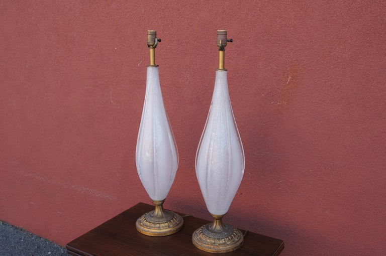 This slender pair of Italian table lamps features handblown white Murano glass drops on carved wooden bases tinted gold.  Sold without shades.
