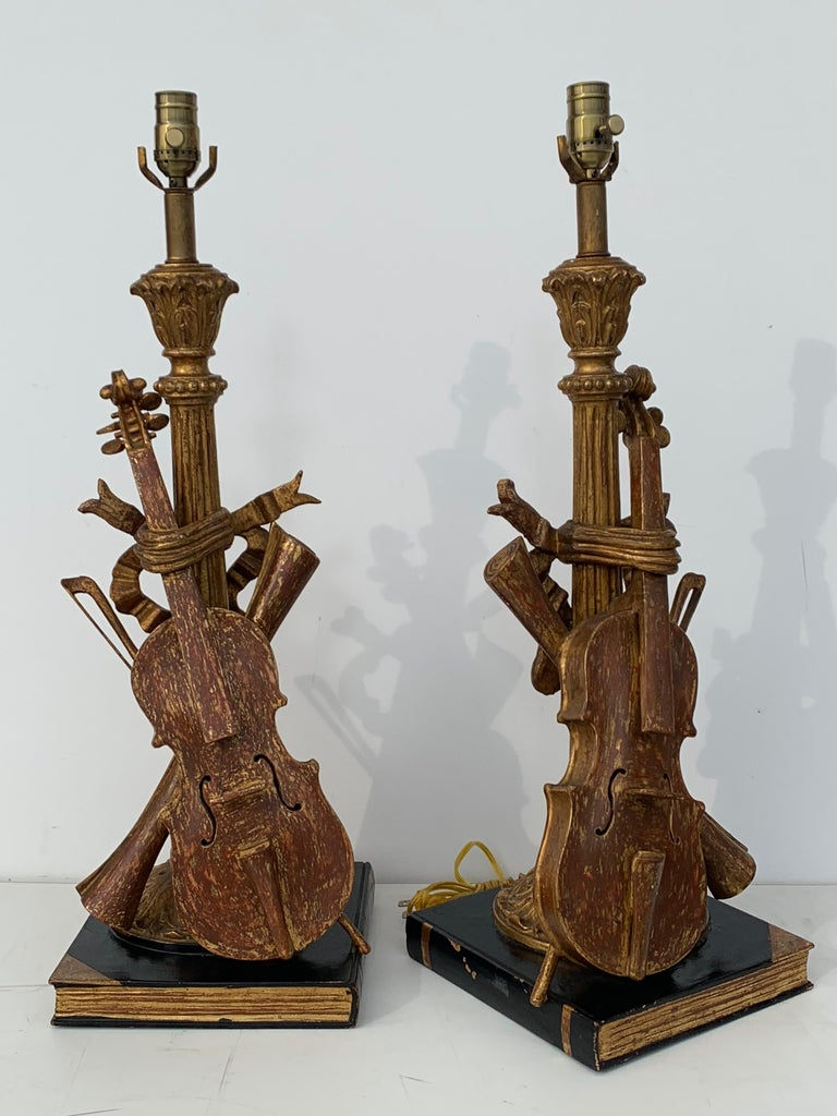 Intricately hand carved and 22-karat gold leafed violin, bow and scroll musical motif lamps. Rewired for USA.