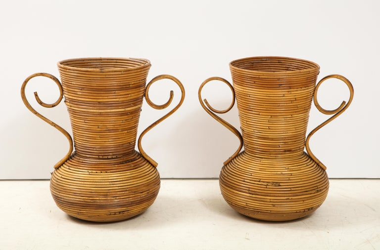 """A pair of Vivai del Sud Greek & Roman inspired rattan two handled vases in the shape of an amphora meaning, """"to carry on both sides."""" Amphorae were traditionally used for carrying and storing solids and liquids. These are an organic interpretation"""