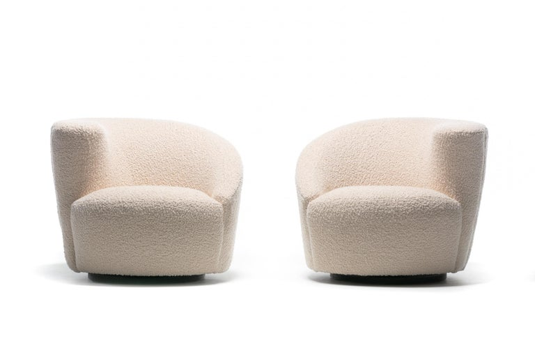 Amongst the most popular Vladimir Kagan designs, these Nautilus swivel lounge chairs are sculptural, comfortable and fun, and were recently professionally reupholstered in cozy Ivory Boucle. Corkscrew shape with sloped back and arm. The Nautilus