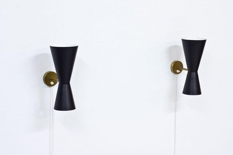 Pair of wall lamps designed by Alf Svensson. Manufactured by Bergboms in Sweden during the 1950s. Black lacquered metal reflectors with brass structure. Good vintage condition with patina and minor signs of wear and age.