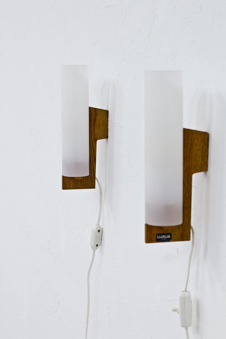Pair of wall lamps designed by Uno and Östen Kristiansson for Luxus. Manufactured in Sweden during the 1960s. Oak frame with acrylic diffuser.