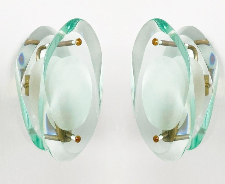 Pair of original light sconces by Max Ingrand for Fontana Arte, Model 2093, Italy, 1960-1961. Organically shaped double lens cut panels of thick Murano profiled polished murano glass with etched glass centers, polished brass mounted. The Model 2093