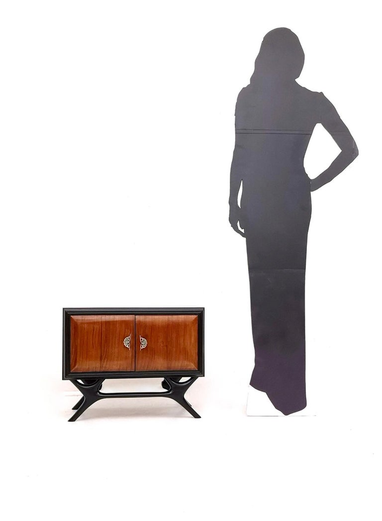 They are made in ebonized wood and walnut and feature brass handles with painted details. These nightstands may show slight traces of use since they're vintage, but they have been perfectly restored, therefore they can be considered as in excellent