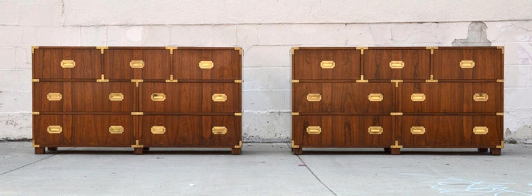 This pair of Campaign style baker chests of drawers each have 7 drawers and are made from bookmatched walnut with brass pulls. The careful book matching can be seen throughout the piece.  While they are listed here as a pair we would also consider