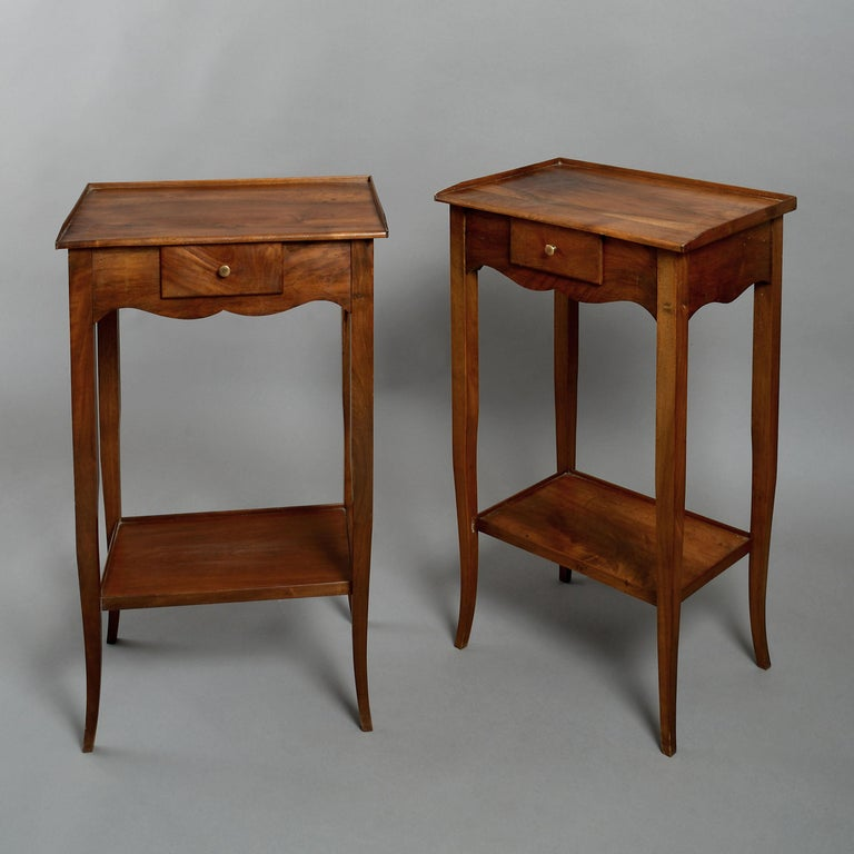 A pair of early 20th century walnut end tables or night stands in the Louis XV manner, each with a rectangular top set above a small central drawer within a shaped apron, all raised on square tapering legs and having a lower shelf.