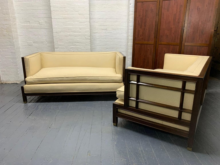 Pair of walnut James Mont sofas. The frame of the sofas is walnut, has lattice sides with a loose cushion seat.