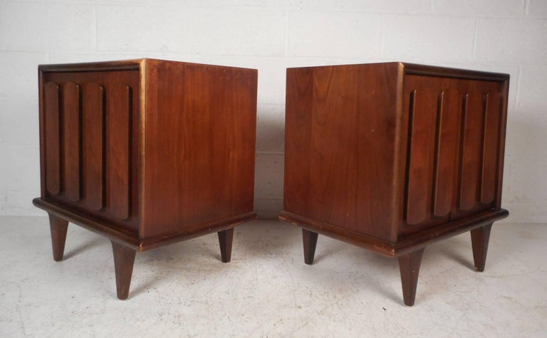 This beautiful pair of Mid-Century Modern nightstands feature two cabinet doors with unusual pulls on the front. The dark walnut finish and tapered legs show quality craftsmanship. These stylish vintage modern case pieces have plenty of room for