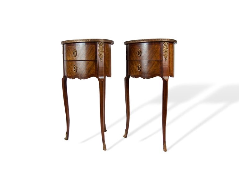 Pair of walnut rosewood banded two-drawer side tables, French, circa 1920, with gilded bronze mounts, sabots, and pierced edging. An unusual and graceful form, tear-drop shaped with three legs and three-sided, sold oak, dovetailed drawers.