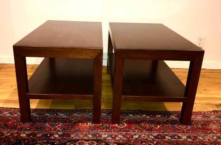 Simple, perfectly proportioned two-tiered walnut side tables, designed by Edward Wormley. Model 4533 from 1945. Both tables retain paper labels and Dunbar brand.