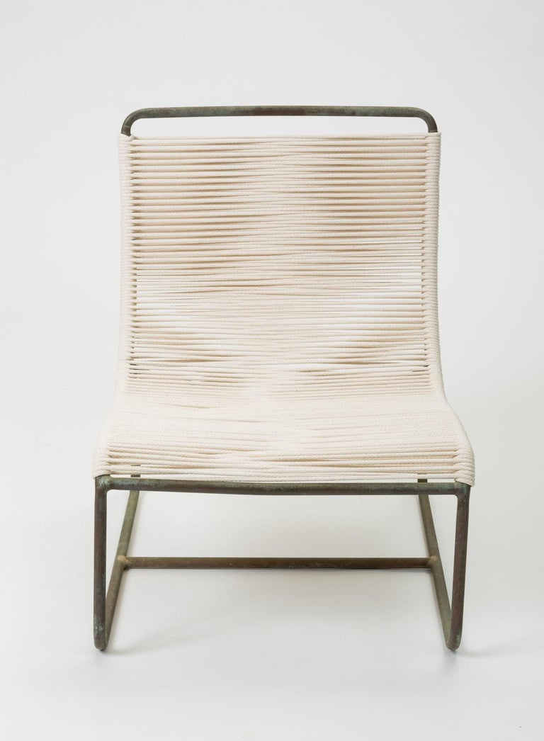 """A pair of low lounge chairs, known as the """"Sleigh Chair"""" by Walter Lamb for Brown Jordan. A continuous length of tubular bronze serves as the frame of a scooped seat, bends beneath the chair to form two runners, and terminates in two delicately"""