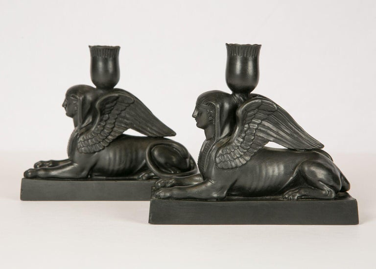 WHY WE LOVE IT: The beauty and strength of woman A Sphinx has the head of a woman, the body of a lion, and a pair of wings. This pair of Wedgwood black basalt sphinxes, are modeled on a rectangular base with a 'lotus' shaped candleholder. The