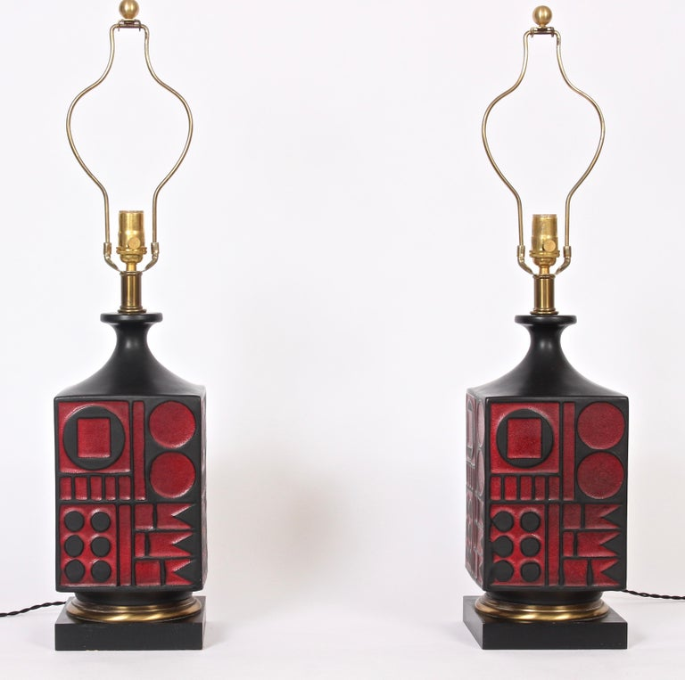 Pair of American midcentury Westwood Industries ceramic table lamps in the style of Tony Paul. Featuring a square black matte glazed smooth textured relief ceramic form with red circle square and flag geometrics on square black enameled wood base