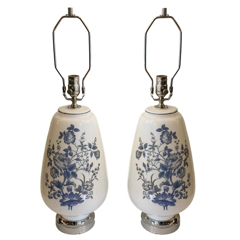 A pair of large circa 1940s French white opaline glass lamps with blue floral decoration.  Measurements: Height of body: 17