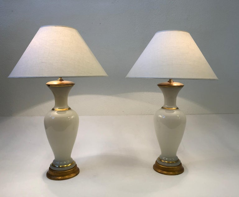 A glamorous pair of Italian white Murano glass and brass table lamps designed by Marbro Lamp Company in the 1960s. The lamps are constructed of Murano glass that's hand painted with real gold stripes, brass hardware and the bases are gilded wood.