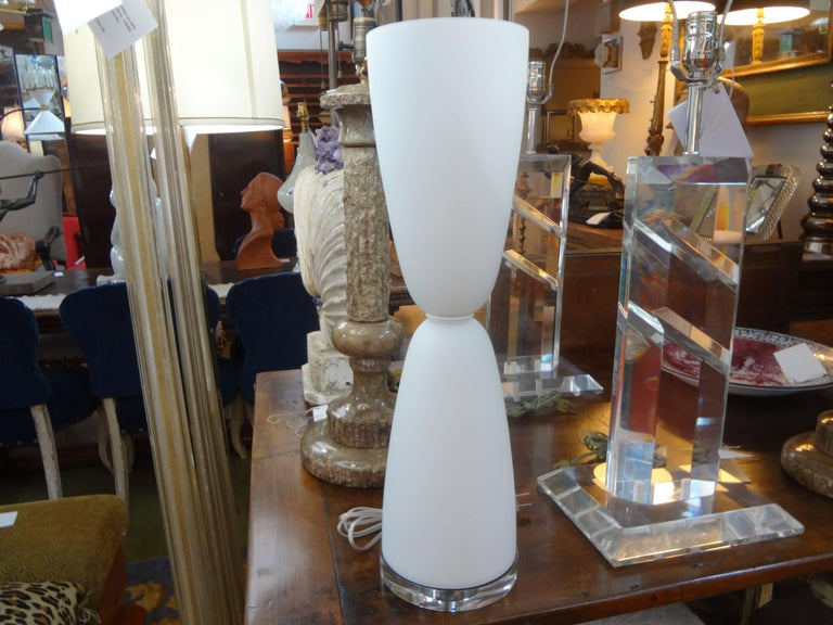 Unusual pair of frosted white Murano glass lamps on Lucite bases. This stunning pair of Mid-Century Modern Italian hourglass shaped lamps have been newly wired for the U.S. market with new porcelain sockets and inline switches. This pair of Murano