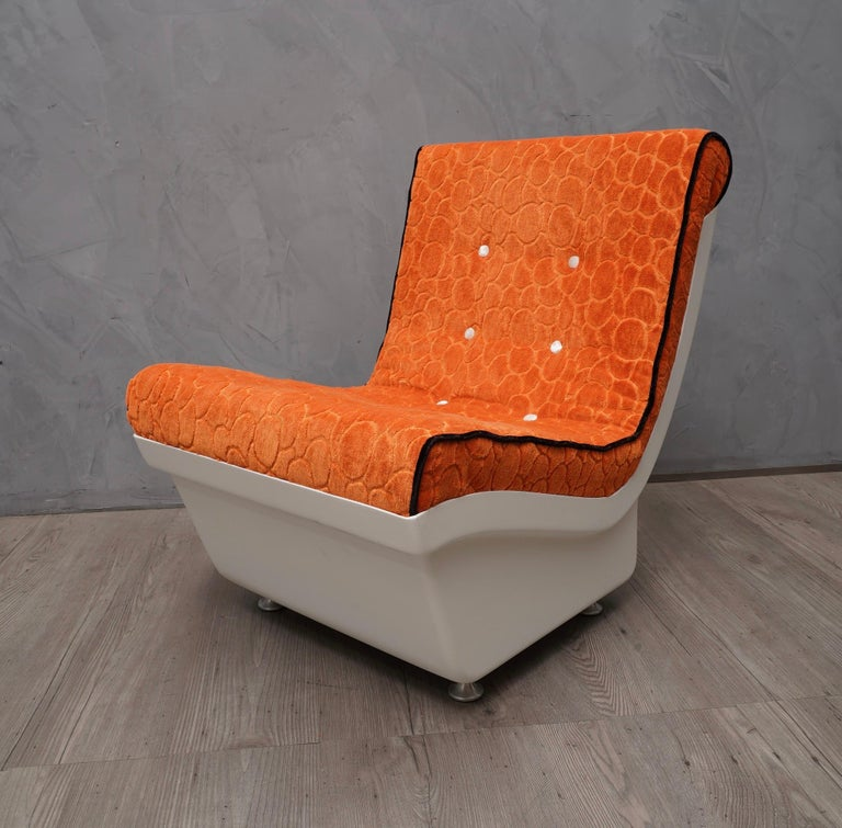 Midcentury design for an armchair out of the ordinary, dressed in a bright and exhilarating orange velvet.  Structure of the shell in white resin / plastic, raised from the ground with small conical feet in satin aluminum. For the new upholstery
