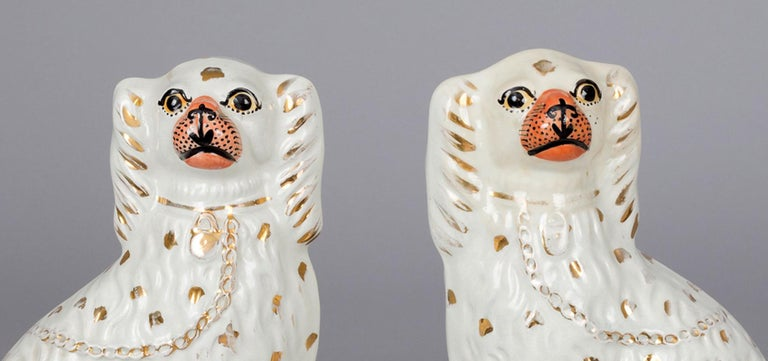Pair of charming white Staffordshire dogs with flesh colored noses, gilded spots, collar and chain.
