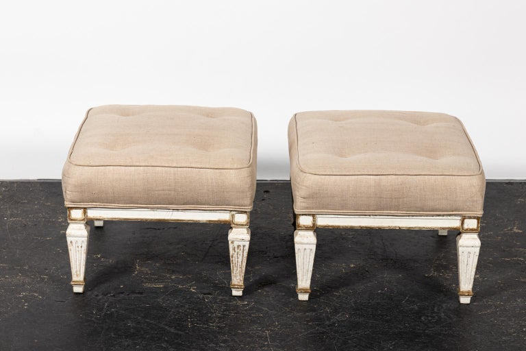 Pair of white upholstered benches with tufted seats and turned legs. Please note of wear consistent with age including paint loss and stains on the upholstery.