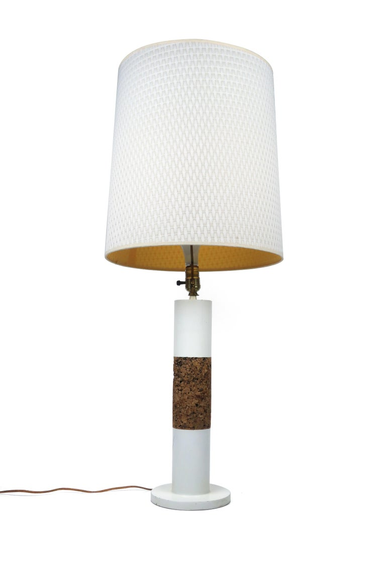 A stunning matched pair of vintage white cylindrical table lamps with cork bands and original white woven fabric shades. Each lamp has a three way switch.