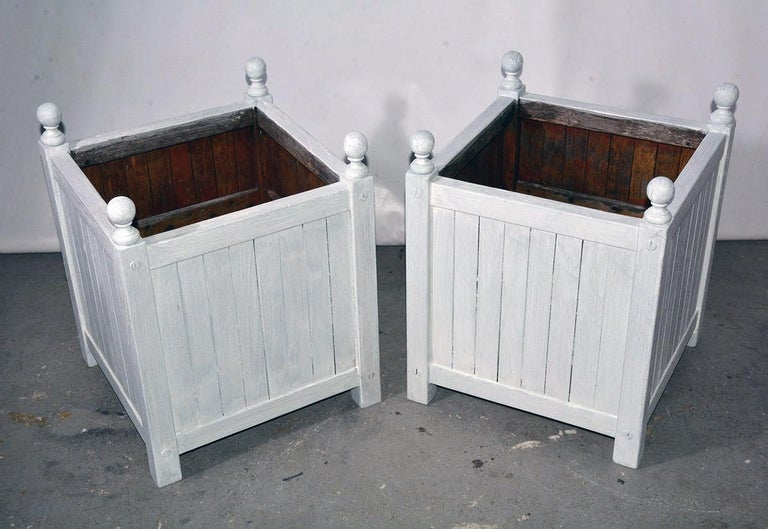 Pair of vintage white washed wooden planter boxes with round decorative finials in the corners.